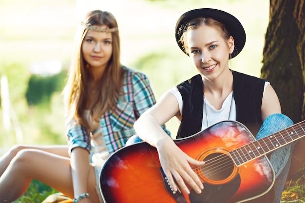 Zwei schöne junge frauen, die gitarre auf einem picknick spielen