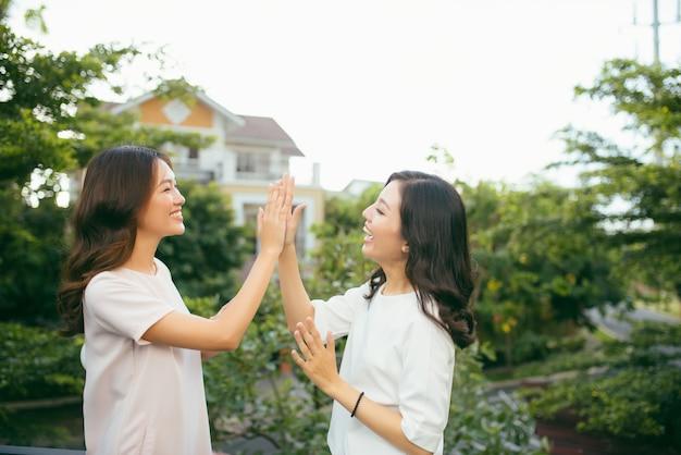 Zwei schöne junge frauen, die high five geben - hübsche mädchen, die draußen stehen und spaß haben - beste freundinnen, die ein versprechen geben