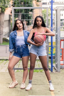 Zwei schöne junge frauen, die lässige sommerkleidung am basketballplatz tragen
