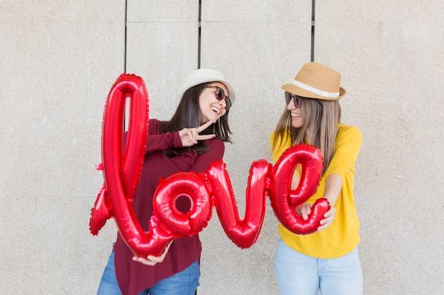 Zwei schöne junge frauen, die spaß draußen mit einem roten ballon mit einer liebeswortform haben. legere kleidung. sie tragen hüte und eine moderne sonnenbrille. lifestyle im freien