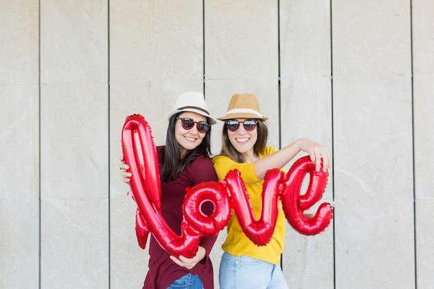 Zwei schöne junge frauen, die spaß draußen mit einem roten ballon mit einer liebeswortform haben. legere kleidung. sie tragen hüte und moderne sonnenbrillen. lifestyle im freien