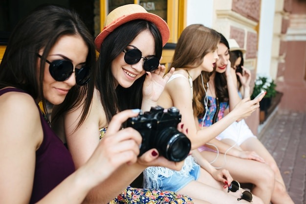 Zwei schöne junge frauen halten vintage-kamera