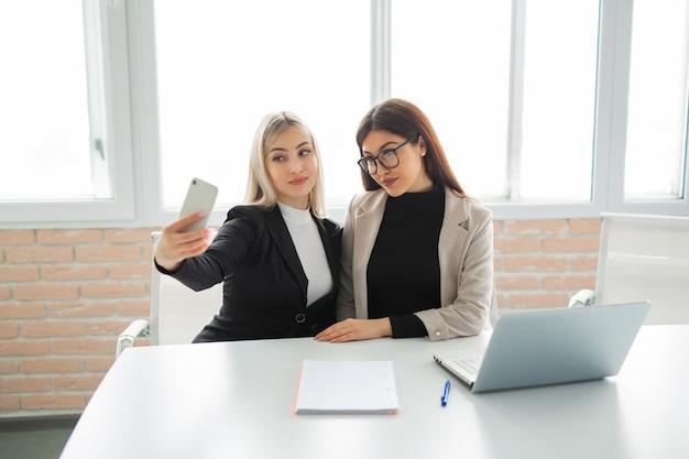 Zwei schöne junge frauen im büro werden am telefon fotografiert