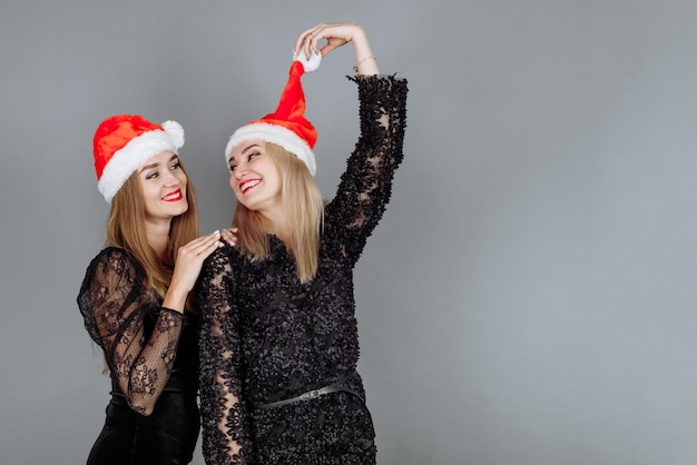 Zwei schöne junge frauen in schwarzen kleidern und weihnachtsmützen, die spaß haben und eine weihnachtsfeier im studio feiern.