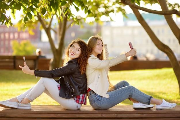 Zwei schöne junge frauen machen gleichzeitig selfies in einem sonnigen park. freundinnen.
