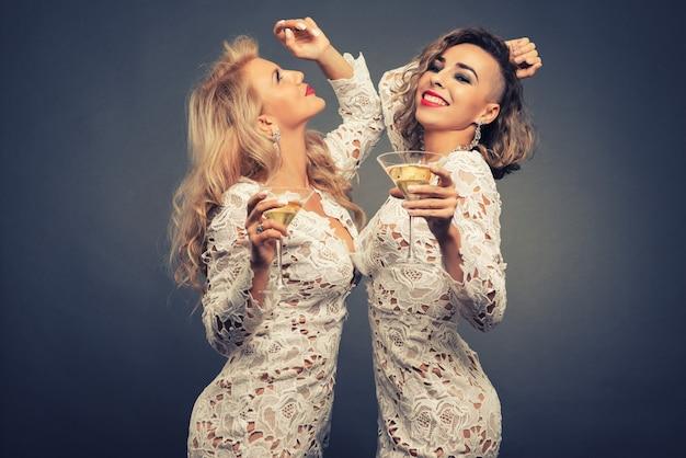 Zwei schöne junge frauen mit martini-brille