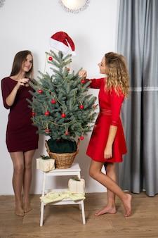 Zwei schöne junge frauen schmücken den weihnachtsbaum