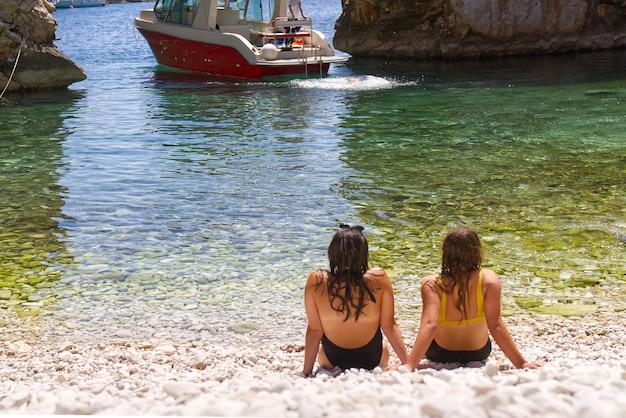 Zwei schöne junge frauenfreunde, die am strand sitzen und sich unterhalten und sich ausruhen