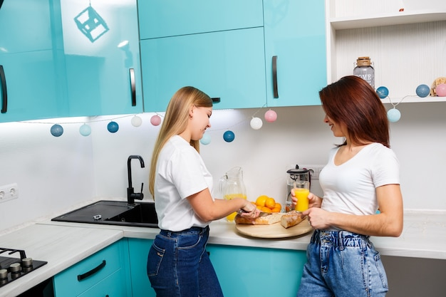 Zwei schöne junge freundinnen stehen zu hause am küchentisch und essen brot und trinken orangensaft
