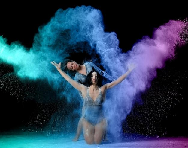 Zwei schöne junge kaukasische frauen in schwarzen bodys mit einer sportfigur tanzen