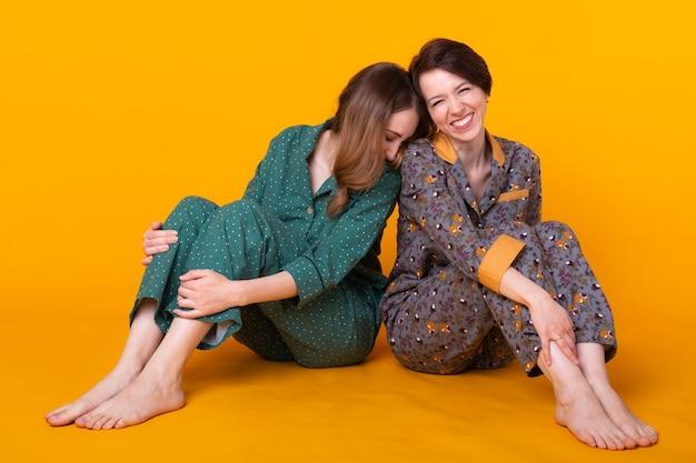Zwei schöne junge mädchen, die bunte pyjamas tragen, die spaßpyjama haben