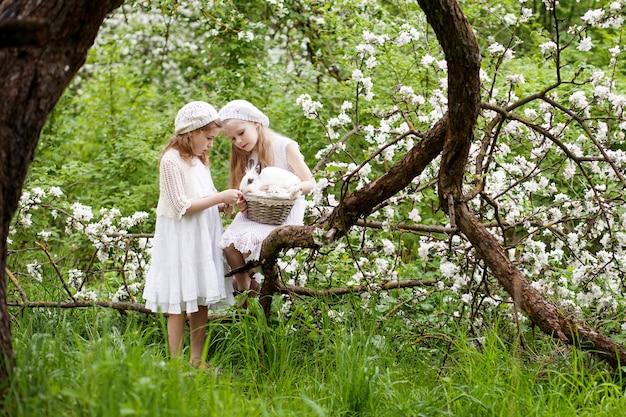 Zwei schöne junge mädchen, die mit weißem kaninchen im frühlingsblütengarten spielen. frühlingsspaß für kinder. osterzeit