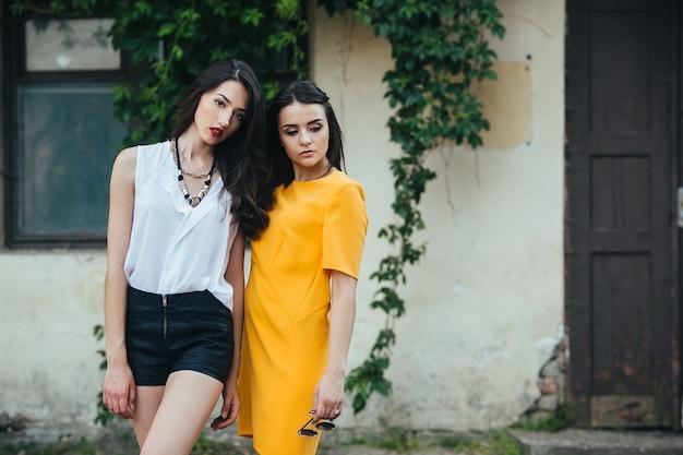 Zwei schöne junge mädchen in kleidern posieren vor haus