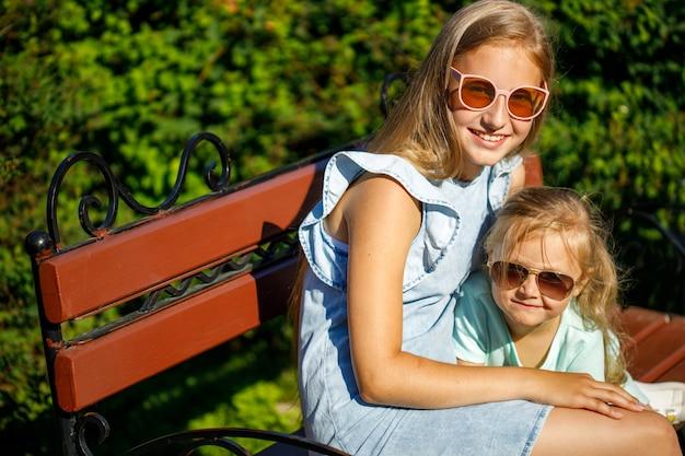 Zwei schöne junge mädchen in sonnengeschützter brille sitzen auf einer parkbank