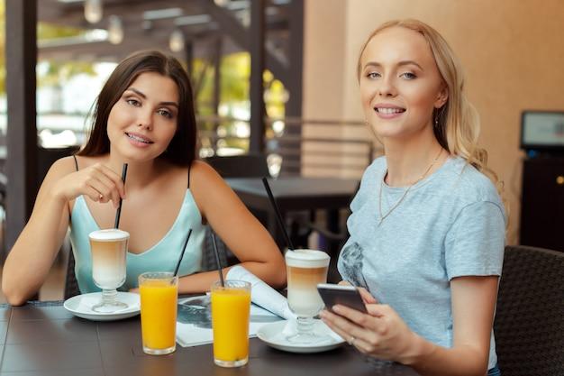 Zwei schöne junge mädchen sitzen am tisch im café