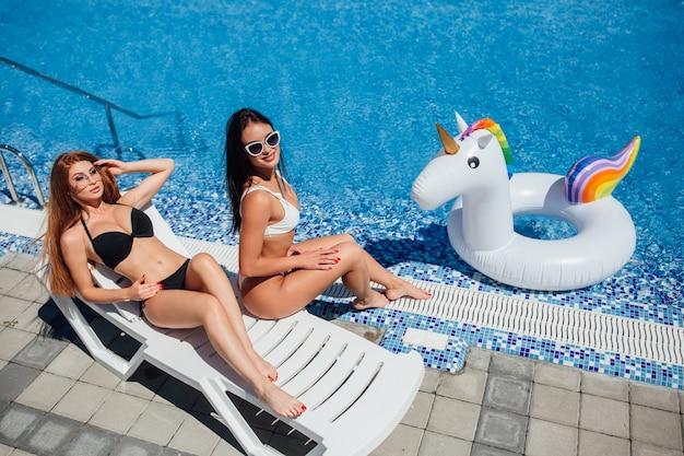 Zwei schöne junge mädchen sonnen sich am pool