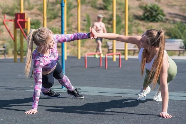 Zwei schöne, junge und sportliche mädchen, die liegestütze auf einem straßenspielplatz machen