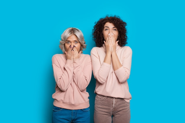 Zwei schöne kaukasische schwestern mit lockigem haar bedecken ihren mund, während sie posieren