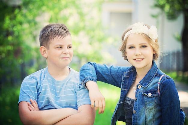 Zwei schöne kinder im freien junge schaut mädchen an