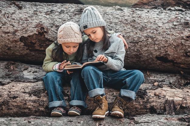 Zwei schöne kleine mädchen, die bücher im herbstwald lesen, sitzen auf einem baumstamm. das konzept von bildung und freundschaft.