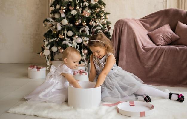 Zwei schöne kleine mädchen in festkleidern sitzen auf einer decke neben dem weihnachtsbaum und öffnen eine geschenkbox