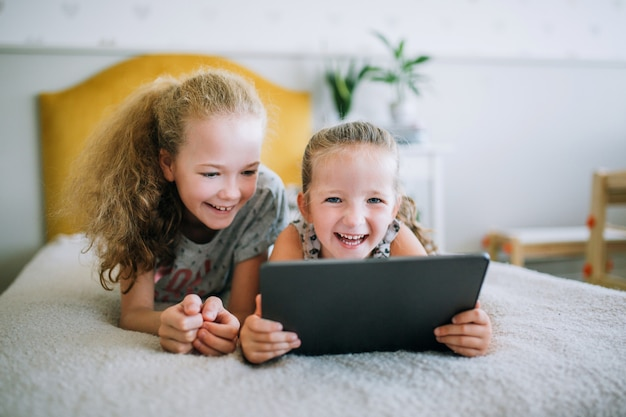 Zwei schöne kleine schwestern, die im bett liegen und den schirm einer tablette, intelligente kinder unter verwendung der intelligenten technologie betrachten