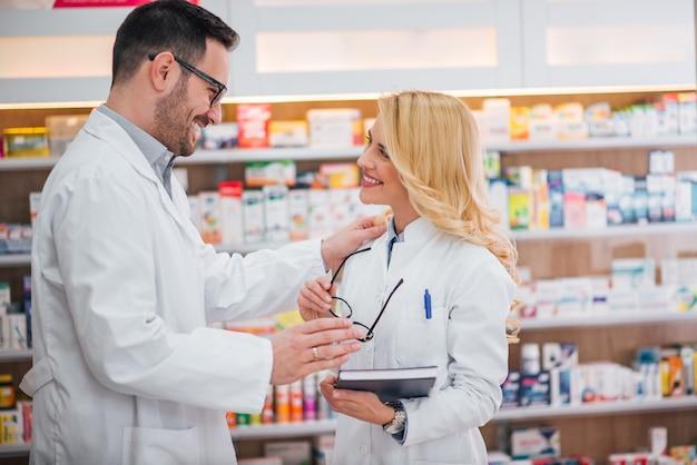 Zwei schöne lächelnde apotheker an der drogerie.