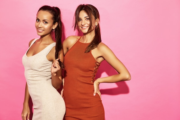 Zwei schöne lächelnde frauenmodelle tragen stilvolles designtrendkleidungs-baumwollkleid, zufällige sommerart für datumssitzungs-wegpartei. brunettegeschäftsfraufrauen, die auf rosa wand aufwerfen