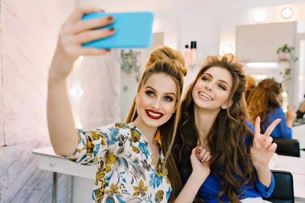 Zwei schöne lächelnde junge frauen, die spaß haben und selfie am telefon im friseursalon machen