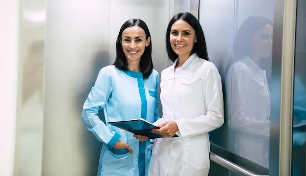 Zwei schöne lächelnde selbstbewusste ärztinnen im aufzug unterhalten sich über eine patientin