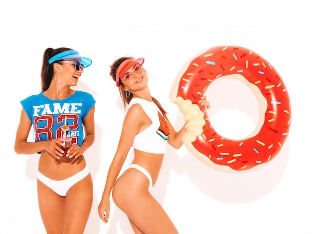 Zwei schöne lächelnde sexy frauen in den weißen sommerunterhosen und -thema. mädchen in sonnenbrille, transparente schirmmütze. modelle, die smoozy getränk des frischen cocktails mit aufblasbarer matratze des donut lilo trinken