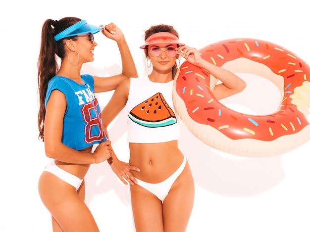 Zwei schöne lächelnde sexy frauen in den weißen sommerunterhosen und -thema. mädchen in sonnenbrille, transparente schirmmütze. positive modelle, die spaß mit krapfen lilo aufblasbarer matratze haben. isoliert