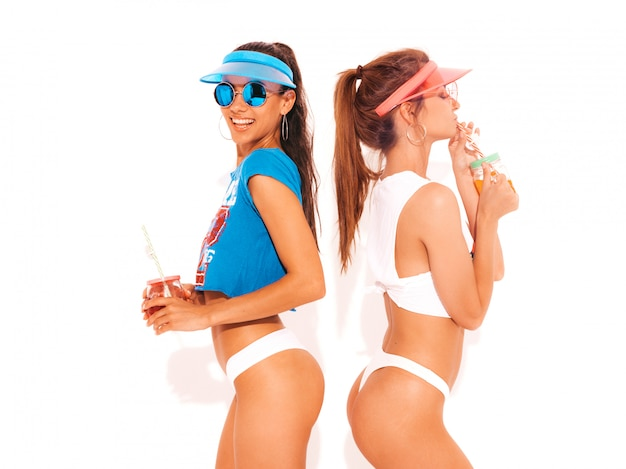 Zwei schöne lächelnde sexy frauen in den weißen sommerunterhosen und -thema. trendy girls in sonnenbrille, transparente schirmmütze. werde verrückt. lustige modelle isoliert. frisches cocktail smoozy getränk trinken