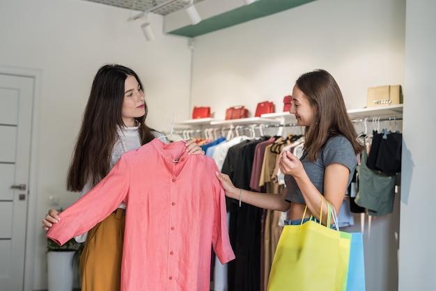 Zwei schöne lächelnfreunde, die im bekleidungsgeschäft auswählen und einkaufen. schwarzer freitag
