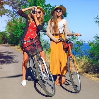 Zwei schöne mädchen der besten freunde, die verrückt werden, spaß haben und nette positive gefühle haben, mit retro-fahrrädern spazieren gehen, sagen sie hallo. trägt stilvolle vintage-outfits und hält eine retro-kamera.