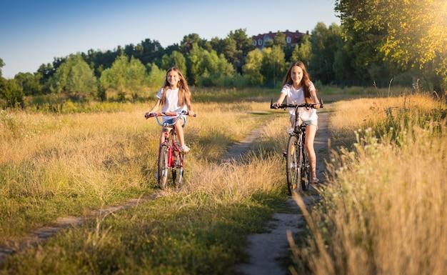 Zwei schöne mädchen, die am sonnigen tag auf der wiese fahrrad fahren