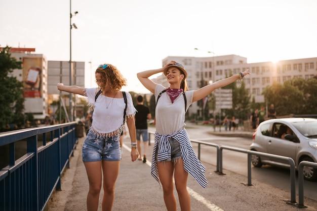 Zwei schöne mädchen, die auf die brücke in der stadt tanzen. auf das musikfestival gehen.