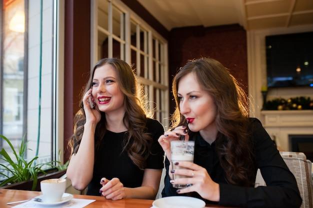 Zwei schöne mädchen, die kaffee trinken und am telefon sprechen