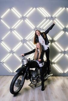 Zwei schöne mädchen, die kostüme von rennfahrern tragen und auf einem motorrad sitzen, im studio