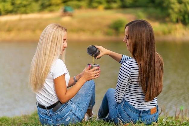 Zwei schöne mädchen genießen die natur und trinken heißen tee am seeufer mit schöner aussicht