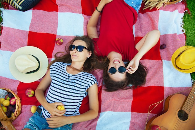 Zwei schöne mädchen in der sonnenbrille, die spaß auf einem picknick in der walddraufsicht hat