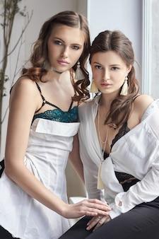 Zwei schöne mädchen in der unterwäsche, die am fenster sitzt
