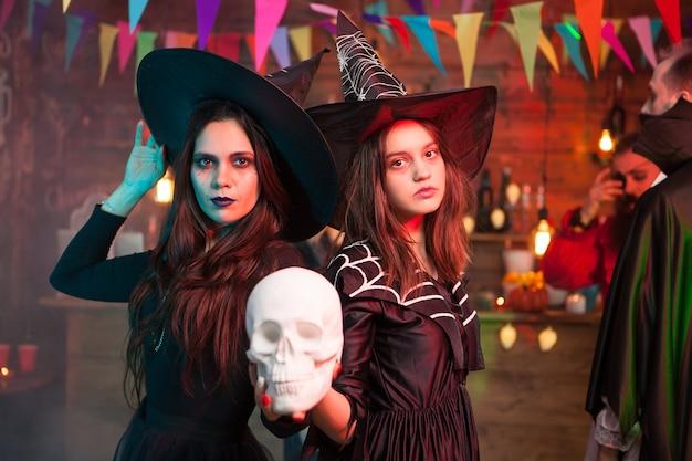 Zwei schöne mädchen in schwarzen kleidern und hexenhüten halten einen totenkopf für die halloween-party. fröhliche hexen.
