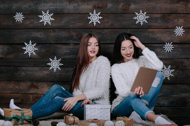 Zwei schöne mädchen mit einer tablette, zwischen geschenken