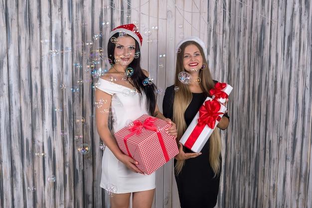 Zwei schöne mädchen mit geschenkboxen posieren im studio
