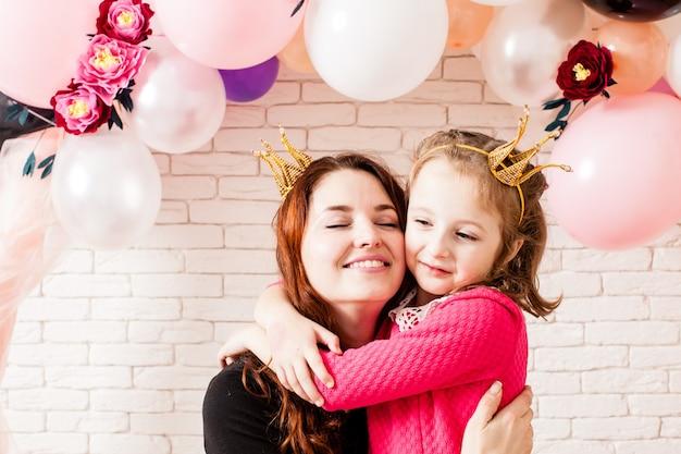 Zwei schöne mädchen mit kronen unter geburtstagsballon und papierblumenbogendekorationen. kindliche photozone zum feiern. mama mit tochter