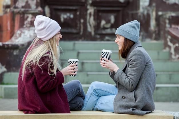 Zwei schöne mädchen mit langen haaren trinken kaffee in der stadt coffee