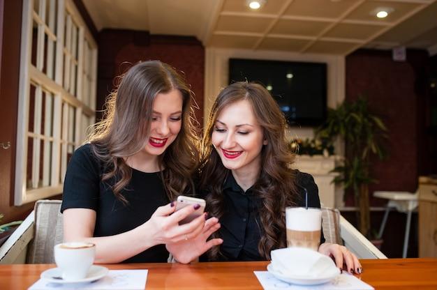 Zwei schöne mädchen trinken kaffee und schauen ins telefon