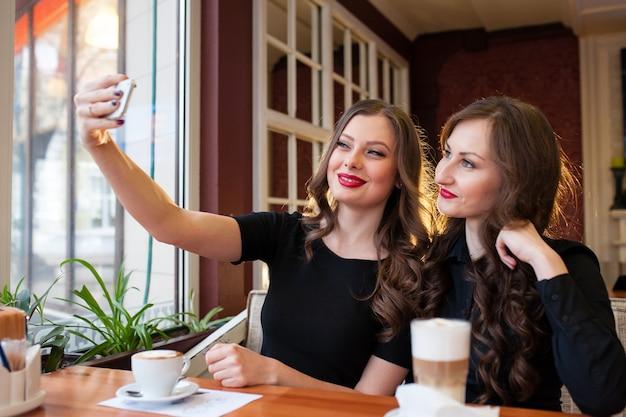 Zwei schöne mädchen tun selfi und trinken kaffee