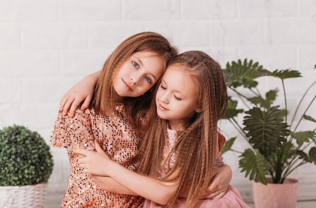 Zwei schöne mädchenschwestern kuscheln sich an eine helle oberfläche